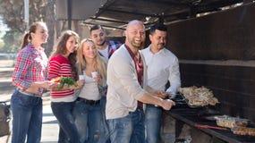 Colegas que hacen la parrilla en la comida campestre Imagen de archivo libre de regalías