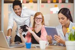 Colegas que sostienen la cámara con la empresaria que usa la tableta digital Fotos de archivo libres de regalías