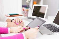 Colegas que usam dispositivos da tecnologia no trabalho Foto de Stock Royalty Free