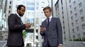 Colegas que usam smartphones para a transação conveniente do dinheiro do app depositar em linha foto de stock royalty free