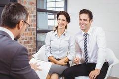 Colegas sonrientes que discuten con el profesional del negocio imagen de archivo libre de regalías