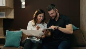 Colegas un hombre y una mujer discutir un proyecto común usando un dibujo y una tableta que se sientan en el sofá en la oficina almacen de metraje de vídeo