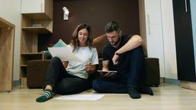Colegas un hombre y una mujer discutir un proyecto común usando un dibujo y una tableta que se sientan en el sofá en la oficina almacen de video