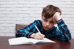 Colegial aburrido que anota una tarea en un cuaderno Estudiar los di imágenes de archivo libres de regalías