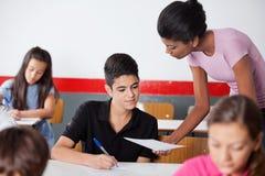 Colegial adolescente de Showing Paper To del profesor durante Fotografía de archivo