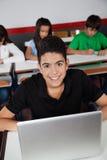 Colegial adolescente feliz que se sienta con el ordenador portátil adentro Foto de archivo libre de regalías