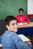 Colegial adolescente feliz que se sienta en el escritorio Imagen de archivo
