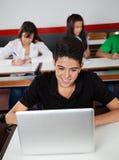 Colegial adolescente feliz que usa el ordenador portátil Fotografía de archivo