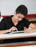 Colegial adolescente feliz que usa la tableta en el escritorio Imágenes de archivo libres de regalías