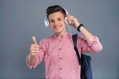 Colegial adolescente optimista que disfruta de la música Foto de archivo libre de regalías