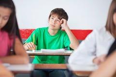 Colegial adolescente pensativo que se sienta en el escritorio Imagen de archivo