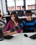 Colegial adolescente que señala en el monitor de computadora Imagen de archivo libre de regalías