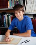 Colegial adolescente que sonríe mientras que se sienta en biblioteca Imagenes de archivo