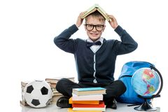 Colegial alegre con el libro en su cabeza que presenta contra los vagos blancos Fotografía de archivo