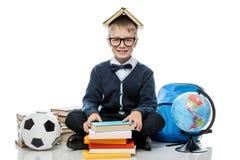 Colegial alegre con los libros y el globo en el fondo blanco en stu Fotografía de archivo libre de regalías