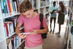 Colegial atento que usa la tableta digital en biblioteca Fotografía de archivo