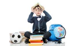 Colegial cansado con el libro en su cabeza que presenta contra el backg blanco Foto de archivo libre de regalías