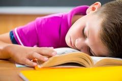 Colegial cansado que duerme en el libro Fotografía de archivo