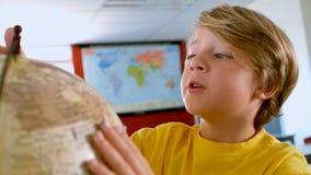 Colegial caucásico lindo que estudia el globo en una sala de clase en la escuela metrajes