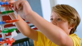 Colegial caucásico lindo que estudia el modelo de la DNA en sala de clase en la escuela almacen de video