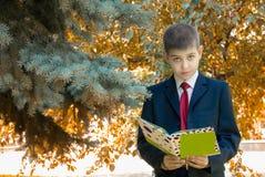 Colegial con el libro en fondo del otoño Fotografía de archivo