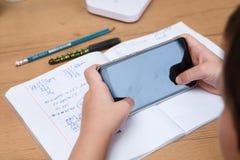 Colegial con el smartphone que hace la preparación en casa Foto de archivo libre de regalías