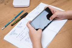 Colegial con el smartphone que hace la preparación en casa foto de archivo