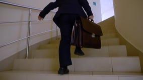 Colegial con la cartera que corre para arriba por las escaleras a la lección en pasillo de la escuela Hombre de negocios joven qu almacen de video