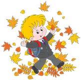 Colegial con las hojas de otoño Foto de archivo libre de regalías