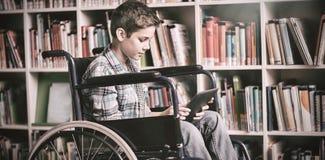 Colegial discapacitado que usa la tableta digital en biblioteca Imagen de archivo libre de regalías
