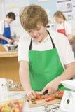 Colegial en una clase de cocinar Foto de archivo libre de regalías