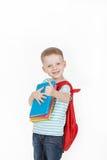 Colegial feliz con la mochila y los libros aislados en el fondo blanco Imagenes de archivo
