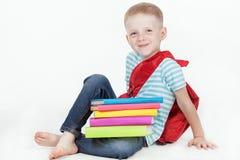 Colegial feliz con la mochila y los libros aislados en el fondo blanco Fotografía de archivo libre de regalías