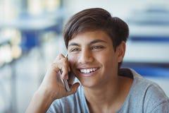 Colegial feliz que habla en el teléfono móvil en sala de clase Foto de archivo libre de regalías
