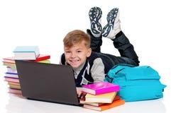 Colegial feliz que miente en piso con el ordenador portátil Fotos de archivo libres de regalías