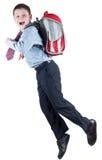 Colegial joven con el bolso de escuela a toda prisa Foto de archivo