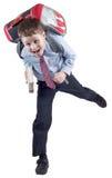 Colegial joven con el bolso de escuela a toda prisa Foto de archivo libre de regalías
