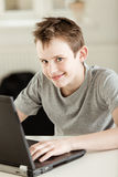 Colegial joven feliz que trabaja en un ordenador portátil Fotos de archivo libres de regalías