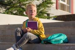 Colegial lindo con libros y una mochila Foto de archivo libre de regalías