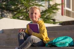 Colegial lindo con libros y una mochila Fotografía de archivo
