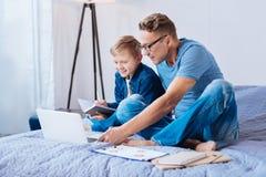 Colegial lindo que hace notas mientras que estudia con el padre Fotografía de archivo libre de regalías