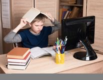 Colegial pre adolescente triste y cansado que se sienta en hacer de trabajo de la tensión Fotografía de archivo