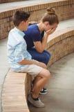Colegial que consuela a su amigo triste en pasos en campus Foto de archivo libre de regalías