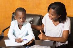 Colegial que estudia con su madre Fotos de archivo libres de regalías