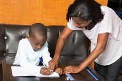 Colegial que estudia con su madre en casa Imagenes de archivo