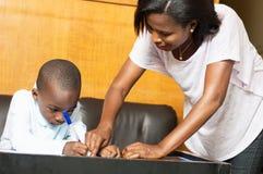 Colegial que estudia con su madre en casa Fotos de archivo