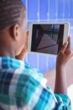 Colegial que fotografía el pasillo a través de la tableta digital Fotos de archivo