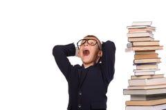 Colegial que grita cerca de la pila enorme de libros Imagen de archivo