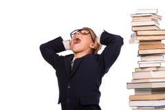 Colegial que grita cerca de la pila enorme de libros Fotografía de archivo