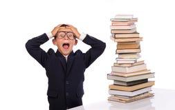 Colegial que grita cerca de la pila enorme de libros Foto de archivo libre de regalías
